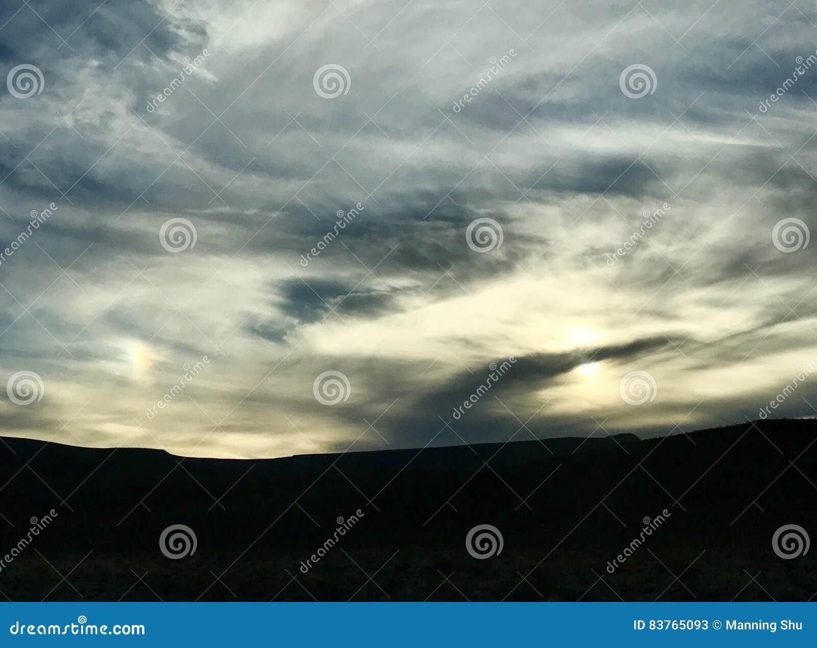 Gefiederte Sonnenaufgang-Sonnenuntergang-Wolken über blauem und gelbem Himmel