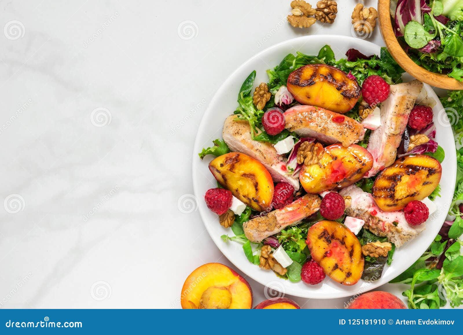 Geflügelsalat mit gegrilltem Pfirsich, Mischsalat, Feta, Himbeeren und Walnüsse in einer Platte Gesunde Nahrung Beschneidungspfad