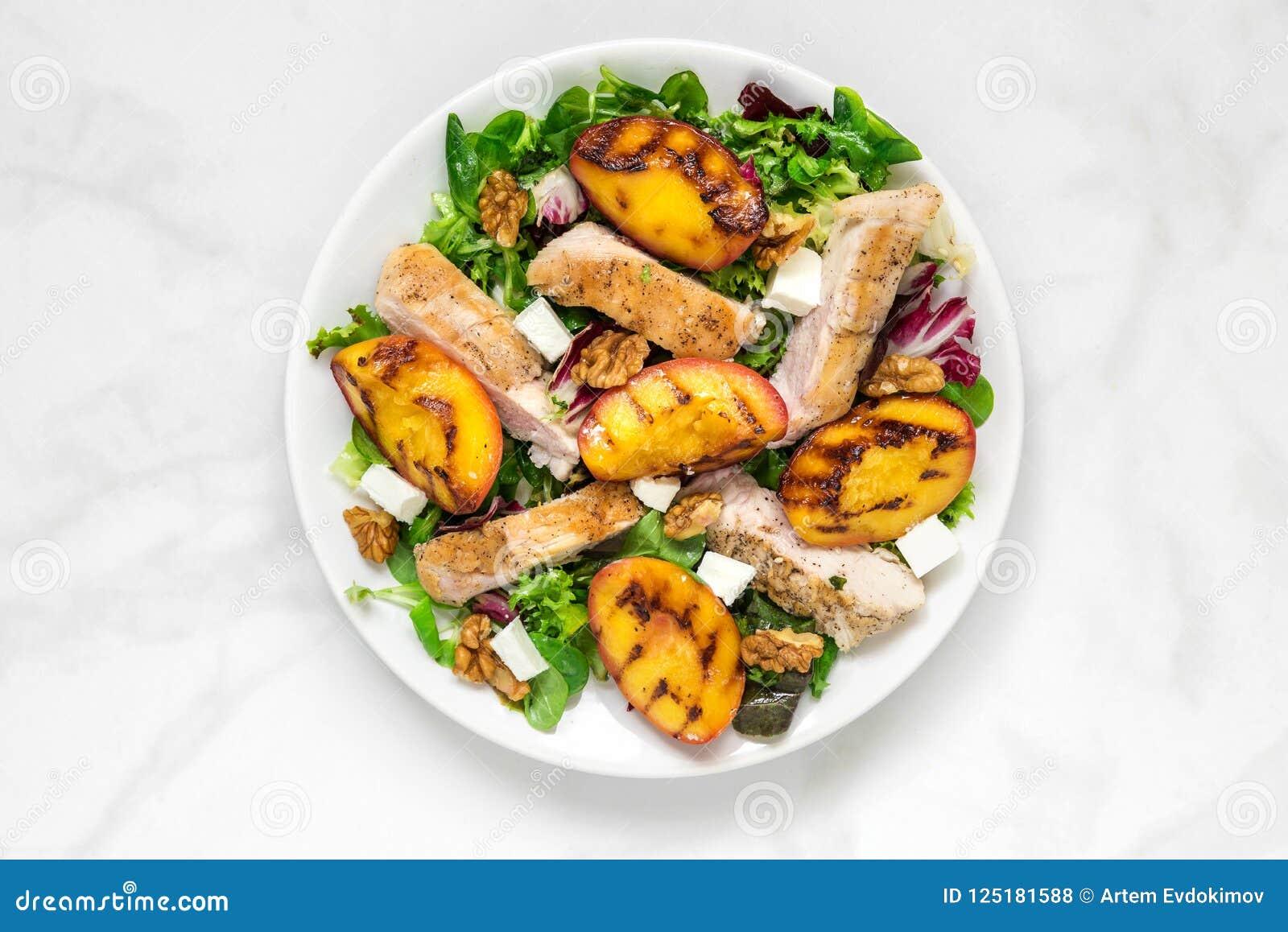 Geflügelsalat mit gegrilltem Pfirsich, Mischsalat, Feta und Walnüsse in einer Platte Gesunde Nahrung