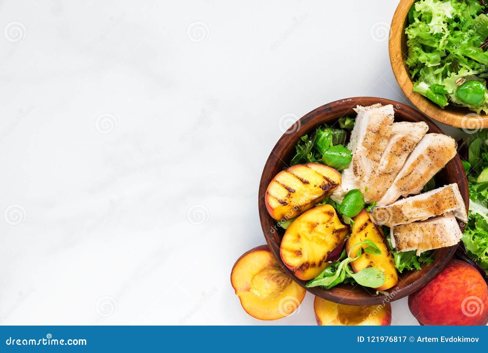 Geflügelsalat mit gegrilltem Pfirsich und Mischsalat in einer Schüssel Gesunde Nahrung Beschneidungspfad eingeschlossen