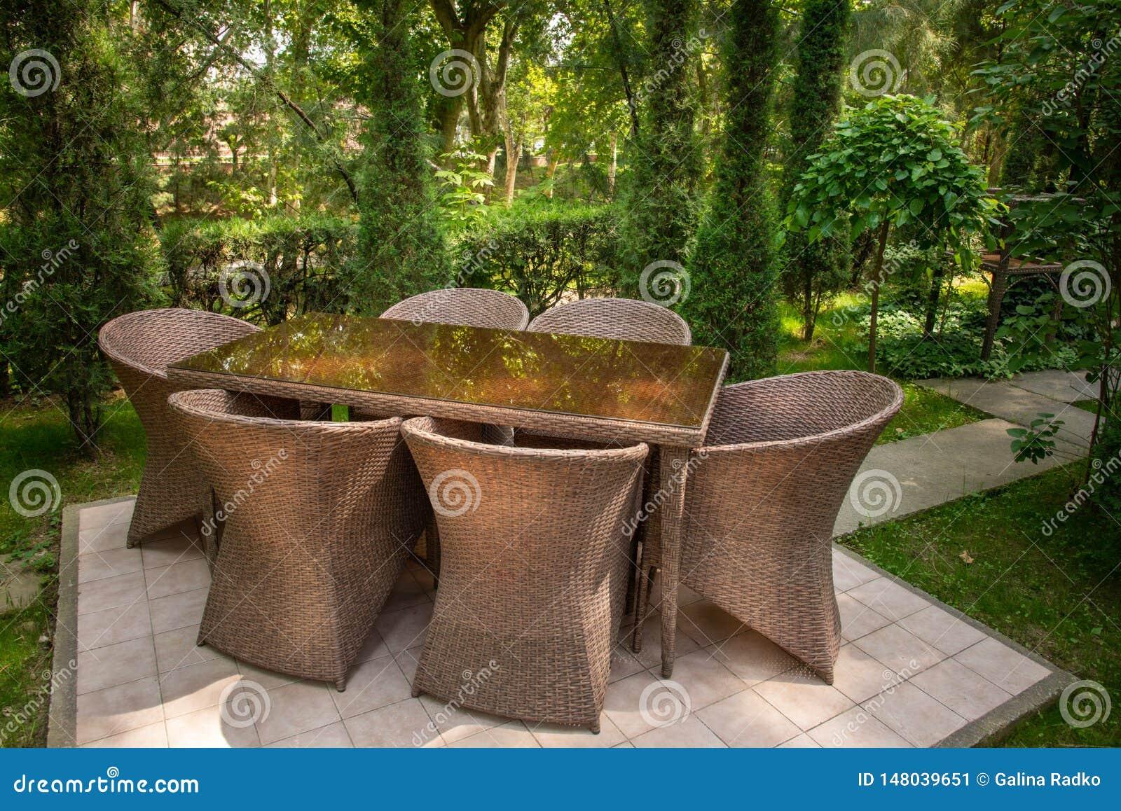 Geflochtene St?hle und Tabelle sind im Garten nahe B?umen