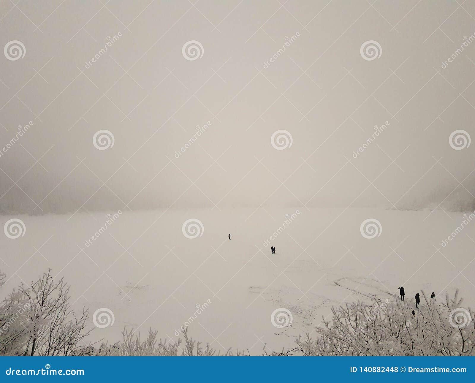 Gefrorenes See Morskie-oko im Winter Leute, die zur Insel auf starkem Eis gehen