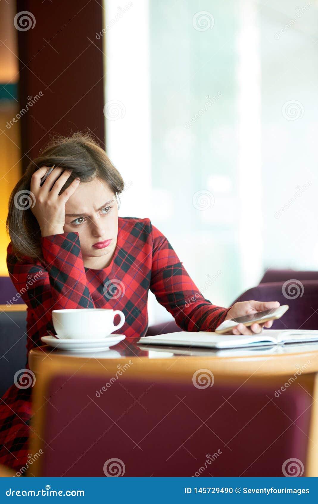 Gefrustreerde jonge vrouwenzitting in coffeeshop