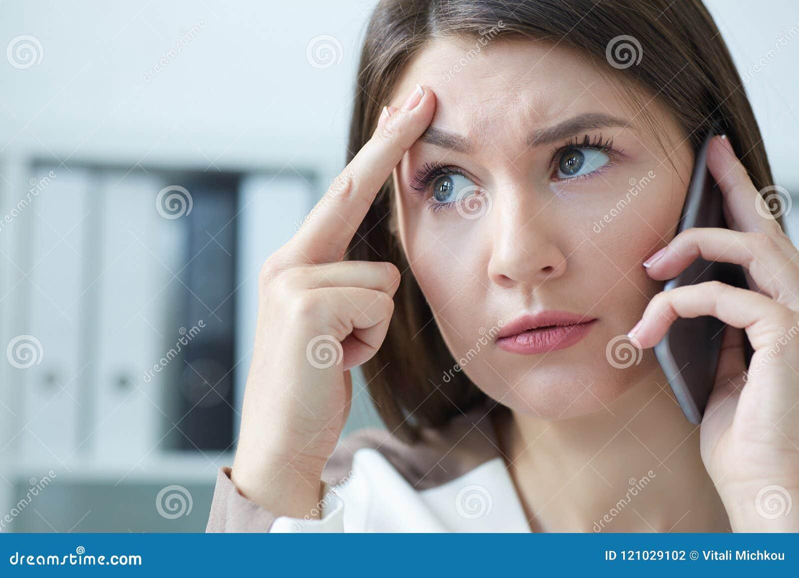 Gefrustreerde onderneemster die op telefoon spreken terwijl het werken aan computer bij bureau in bureau