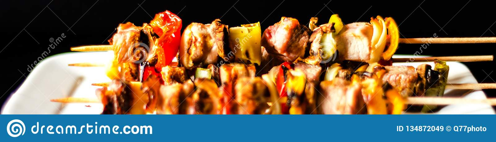 Gegrillte Aufsteckspindeln des Fleisches und des Gemüses auf einem hölzernen Brett-, bunten und geschmackvollenteller
