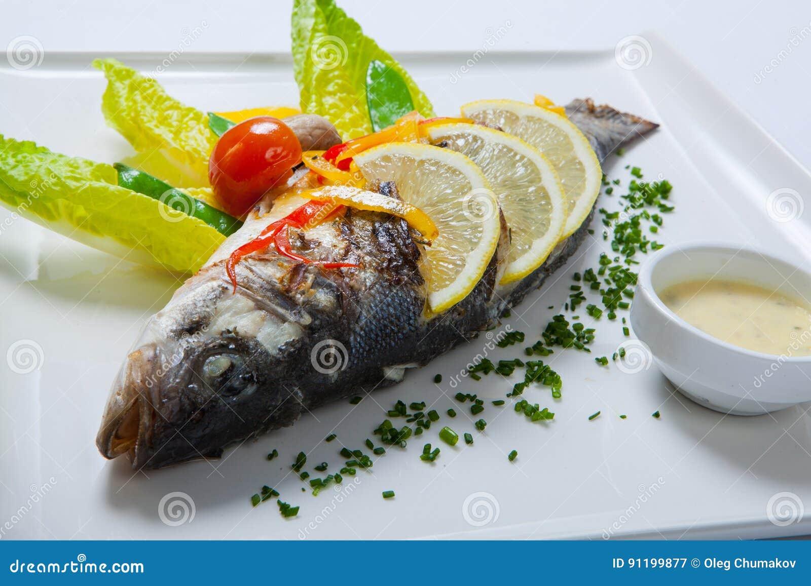 Gegrillte ganze Fische verziert mit den Blättern der Kopfsalat- und Kirschtomate, gedient mit Knoblauchsoße Gebratene ganze Fisch