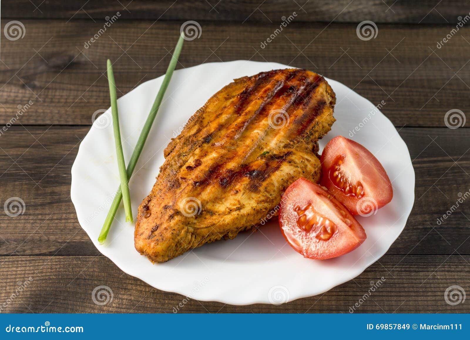 Gegrillte gesunde Hühnerbrust diente mit Tomate und frischem Schnittlauch auf weißer Platte auf Holztisch