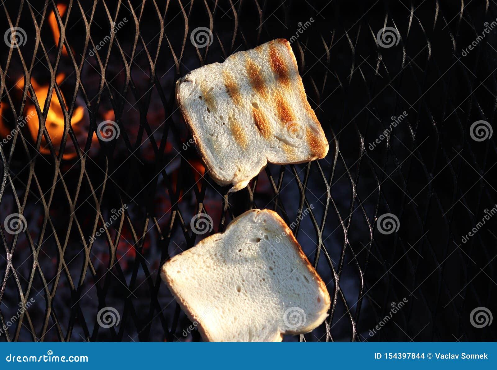 Gegrillter weißer Toast auf speziellem schwarzem Grill für tadellos knusperige Zartheit Toast auf der mittleren Flamme braten gem
