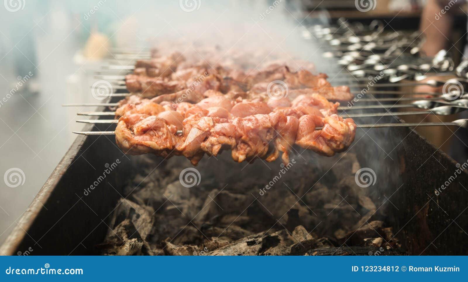 Gegrilltes Grillfleisch auf Aufsteckspindeln über Feuer mit dem Rauche, der auf einer Kohle kocht