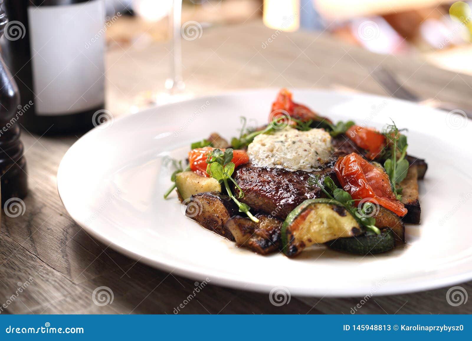 Gegrilltes Steak der Mittelrippe vom Rind mit Kr?uterbutter und gegrilltem Gem?se diente auf einer wei?en Platte