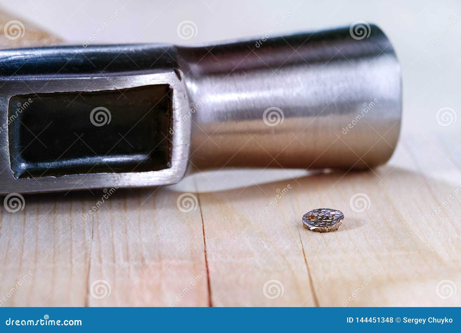 Gehämmerter Nagel und Hammer auf Holzoberfläche