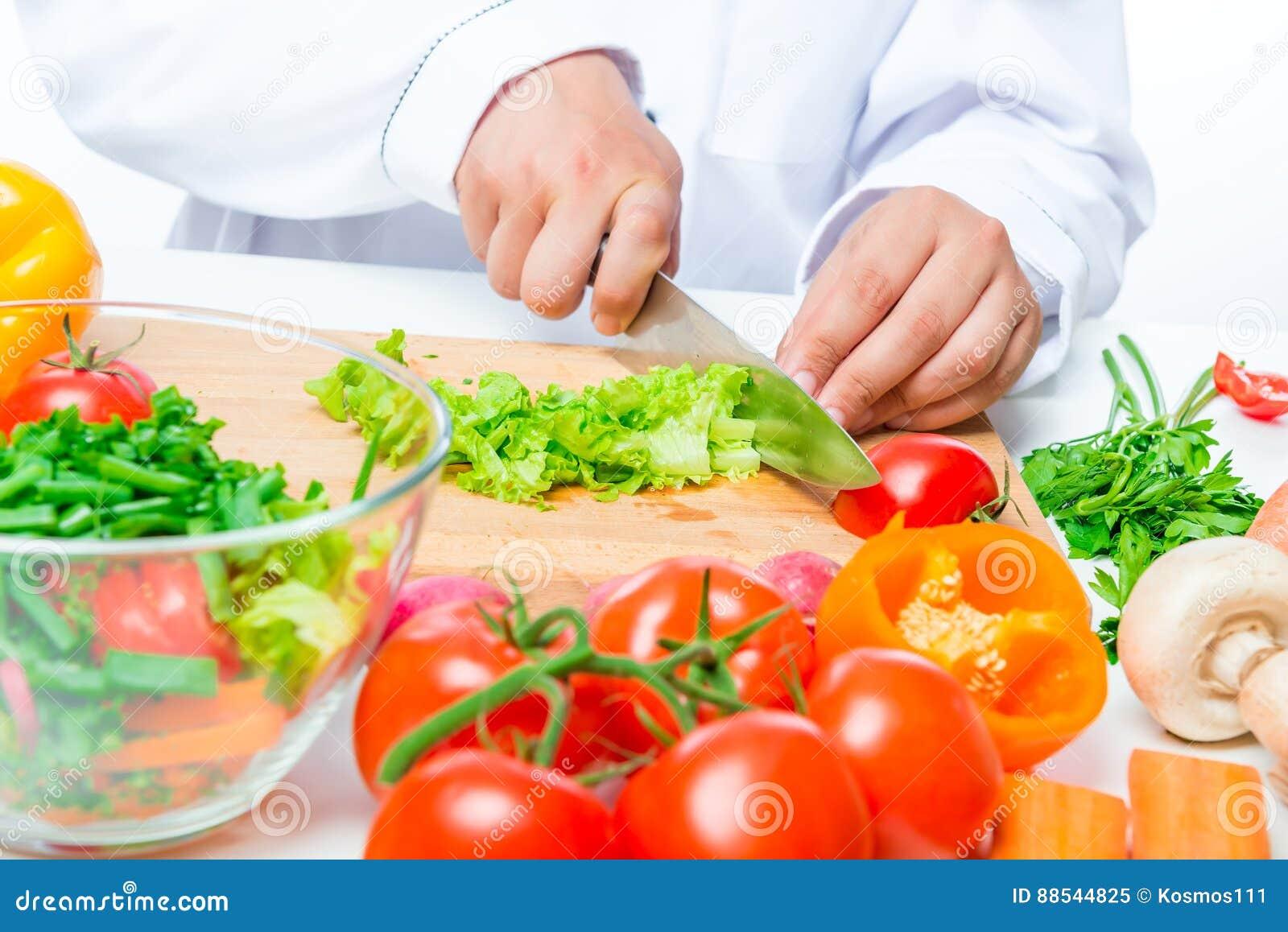 Gehackte Kopfsalat- und Kochhand mit einem Messer