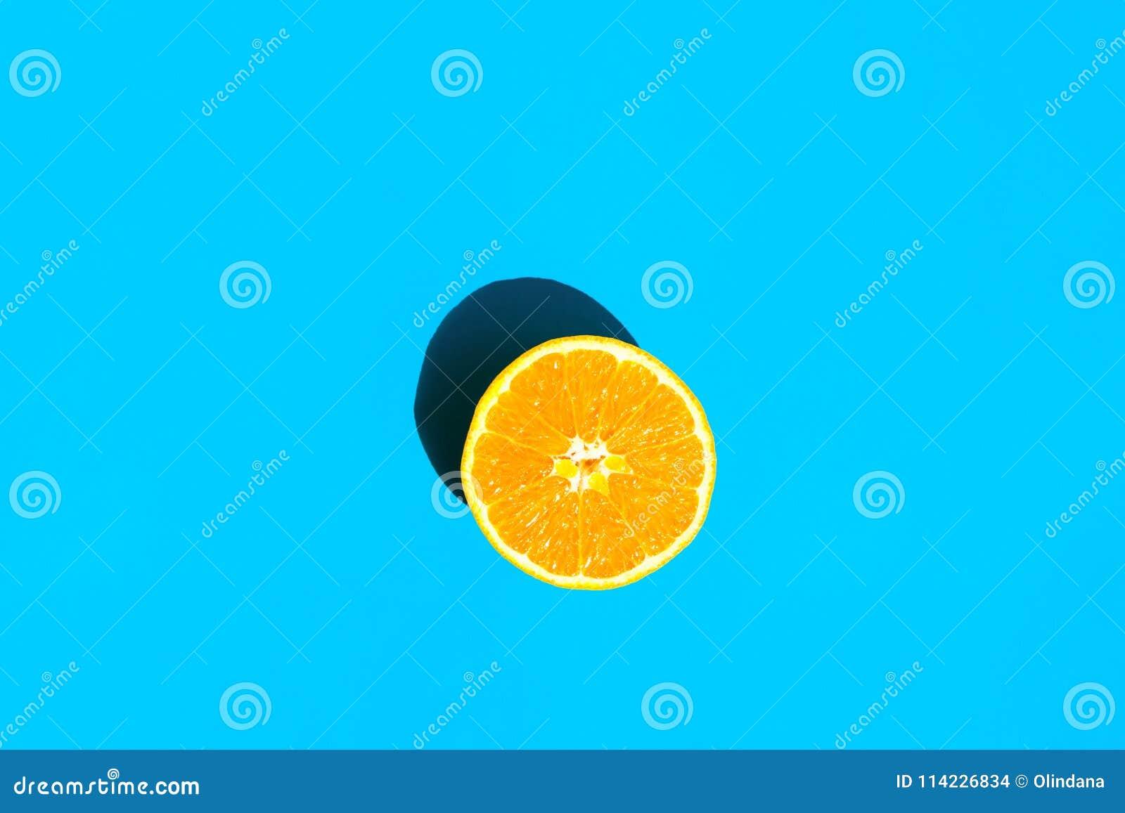 Gehalveerde Rijpe Sappige Sinaasappel op Blauwe Achtergrond Heldere Ruwe Zonlicht Diepe Schaduw Trillende Neonkleuren De Manier v