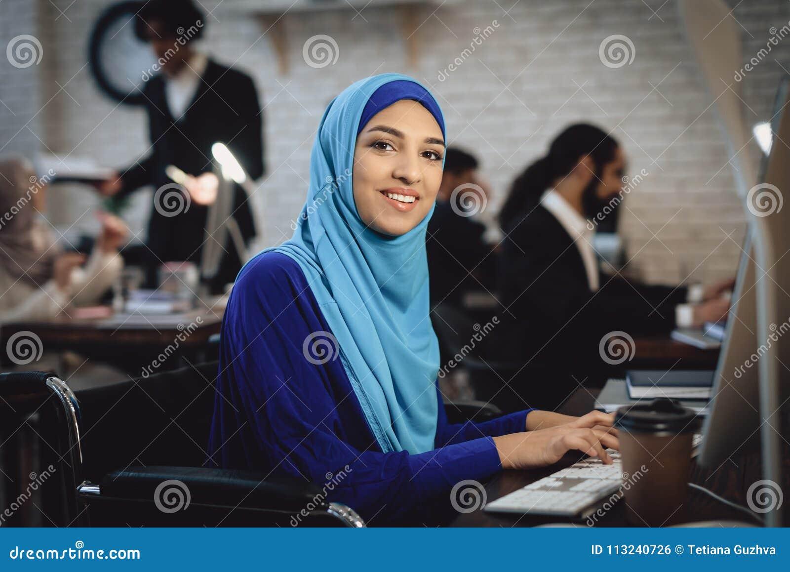 Gehandicapte Arabische vrouw in rolstoel die in bureau werken De vrouw werkt aan bureaucomputer