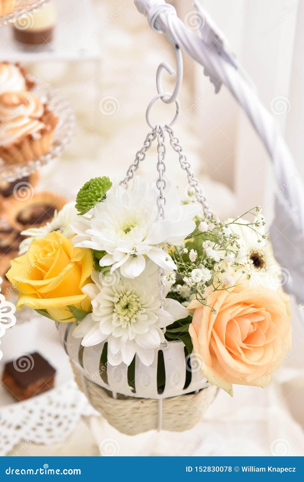 Gehangen bloemenregeling met witte en gele rozen