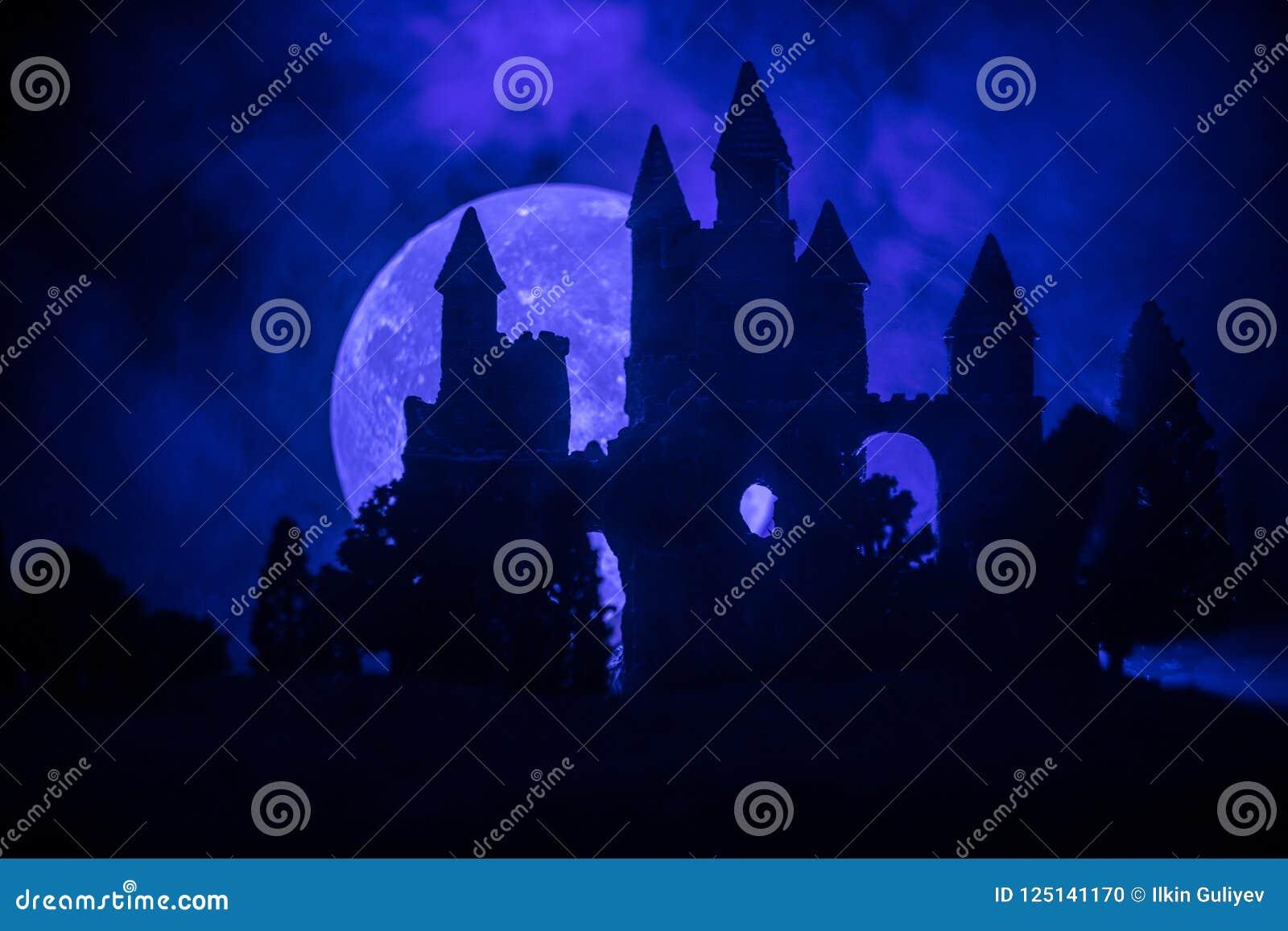Geheimzinnig middeleeuws kasteel in een nevelige volle maan Verlaten gotisch stijl oud kasteel bij nacht
