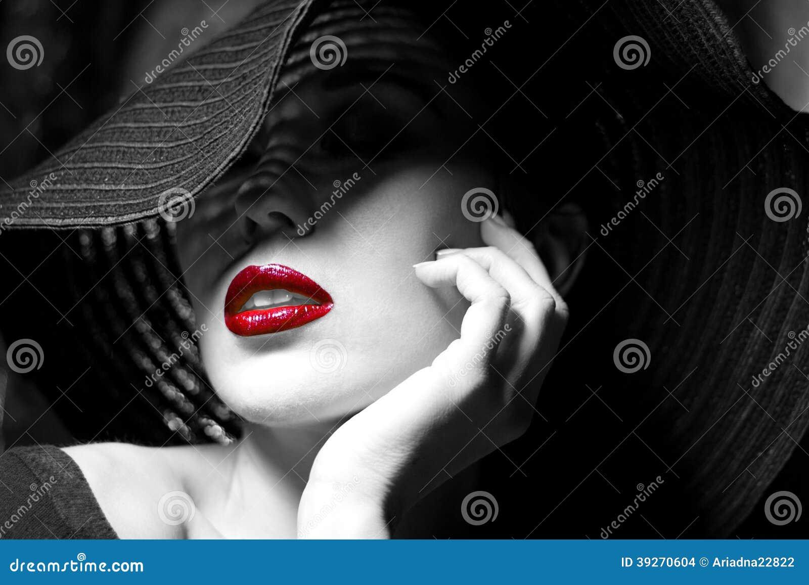 Geheimzinnige vrouw in zwarte hoed. Rode lippen