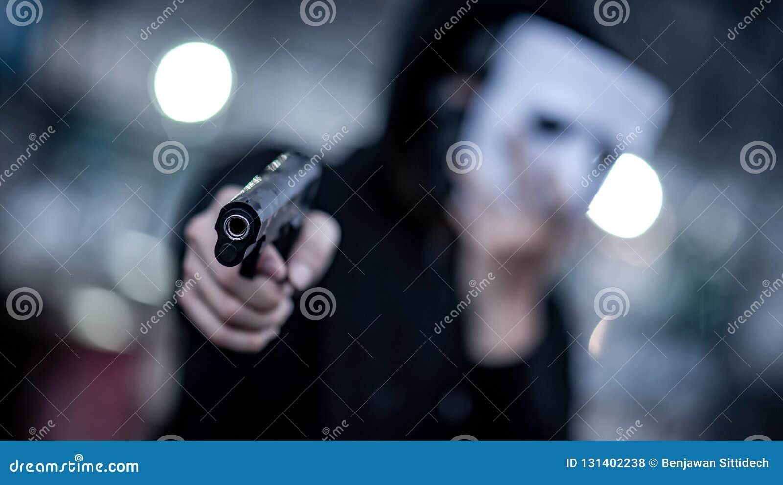Geheimzinnigheid hoodie mens in wit masker die kanon richten Misdaad en geweldconcepten Nadruk op kanon