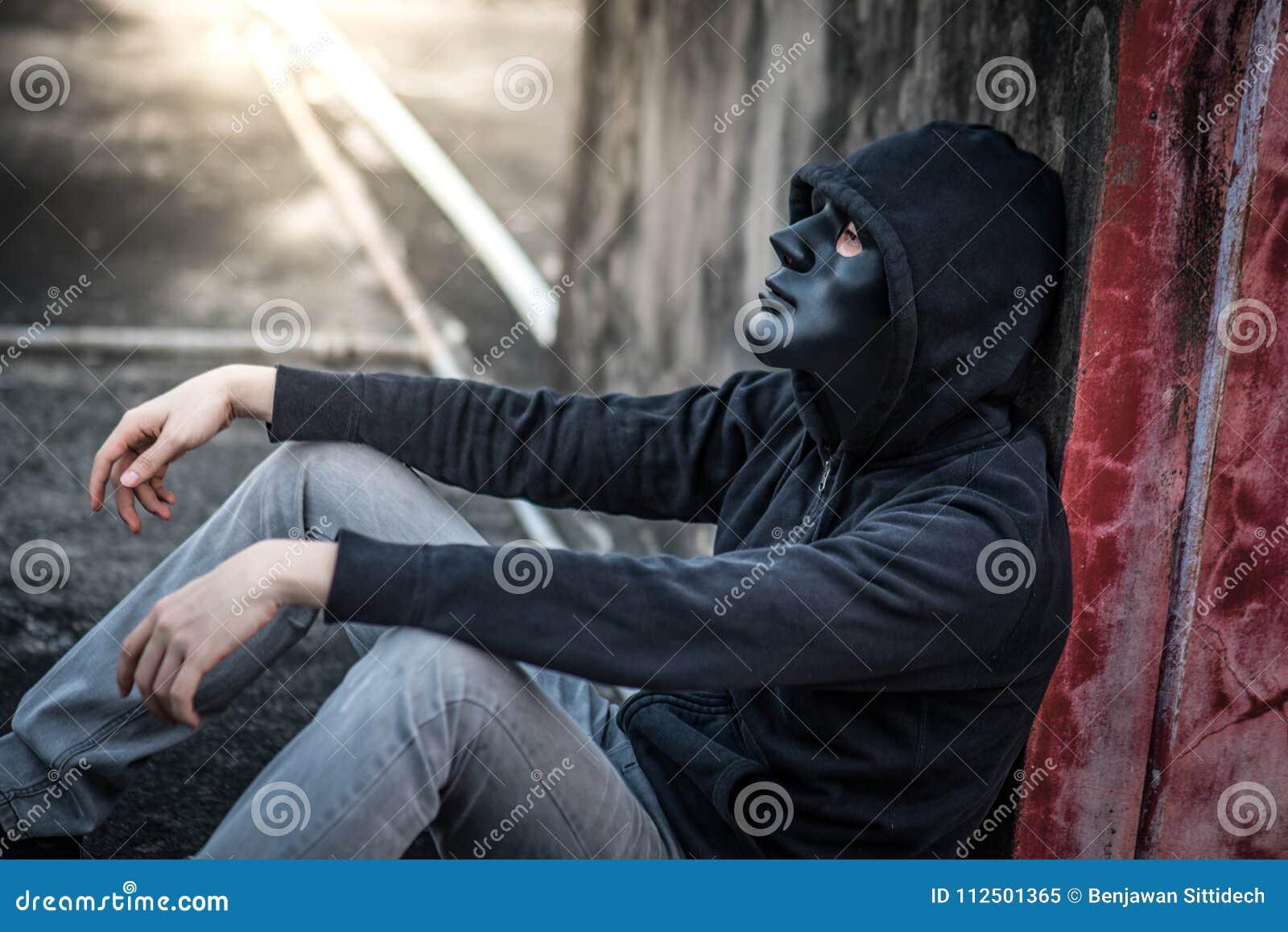 Geheimzinnigheid mens in zwarte maskerzitting in verlaten de bouw gevoel