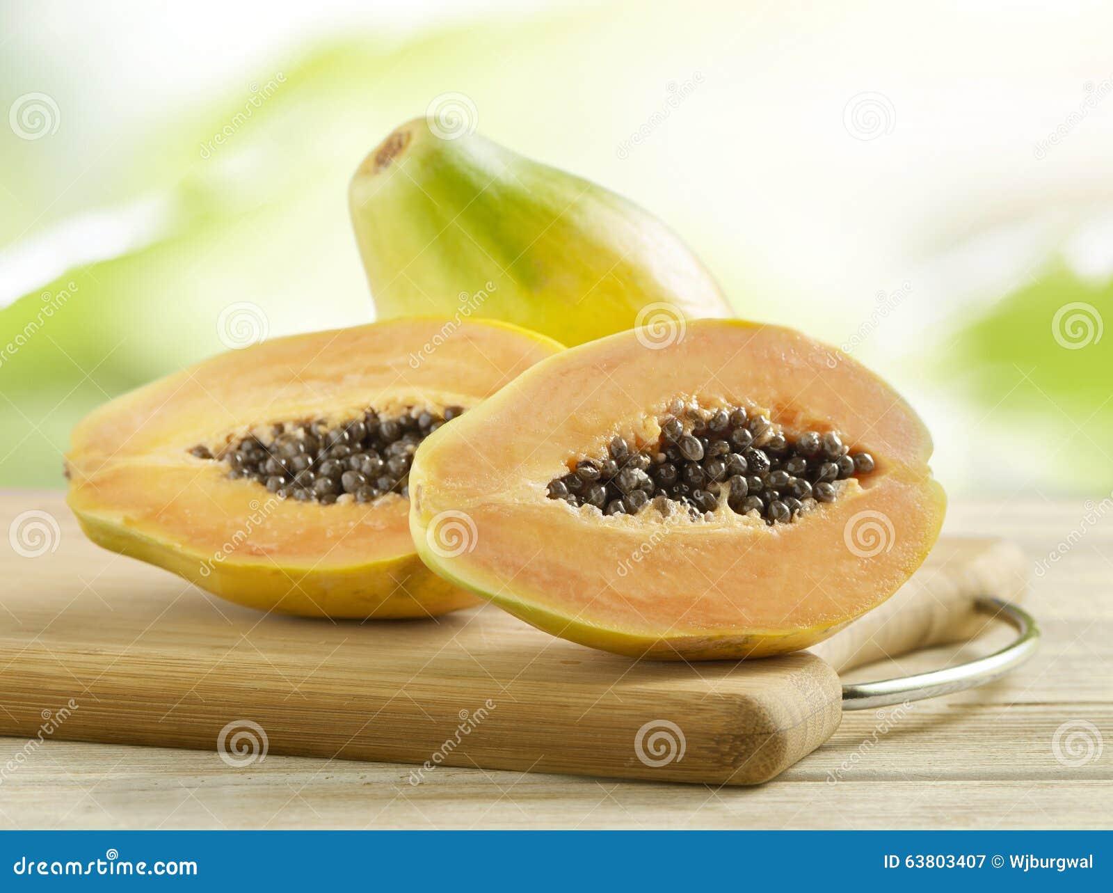 Gehele en gehalveerde papaja s op een houten raad