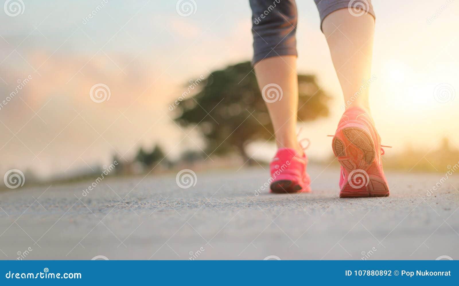 Gehende Übung der Athletenfrau auf Landstraße in Sonnenuntergang backgroun