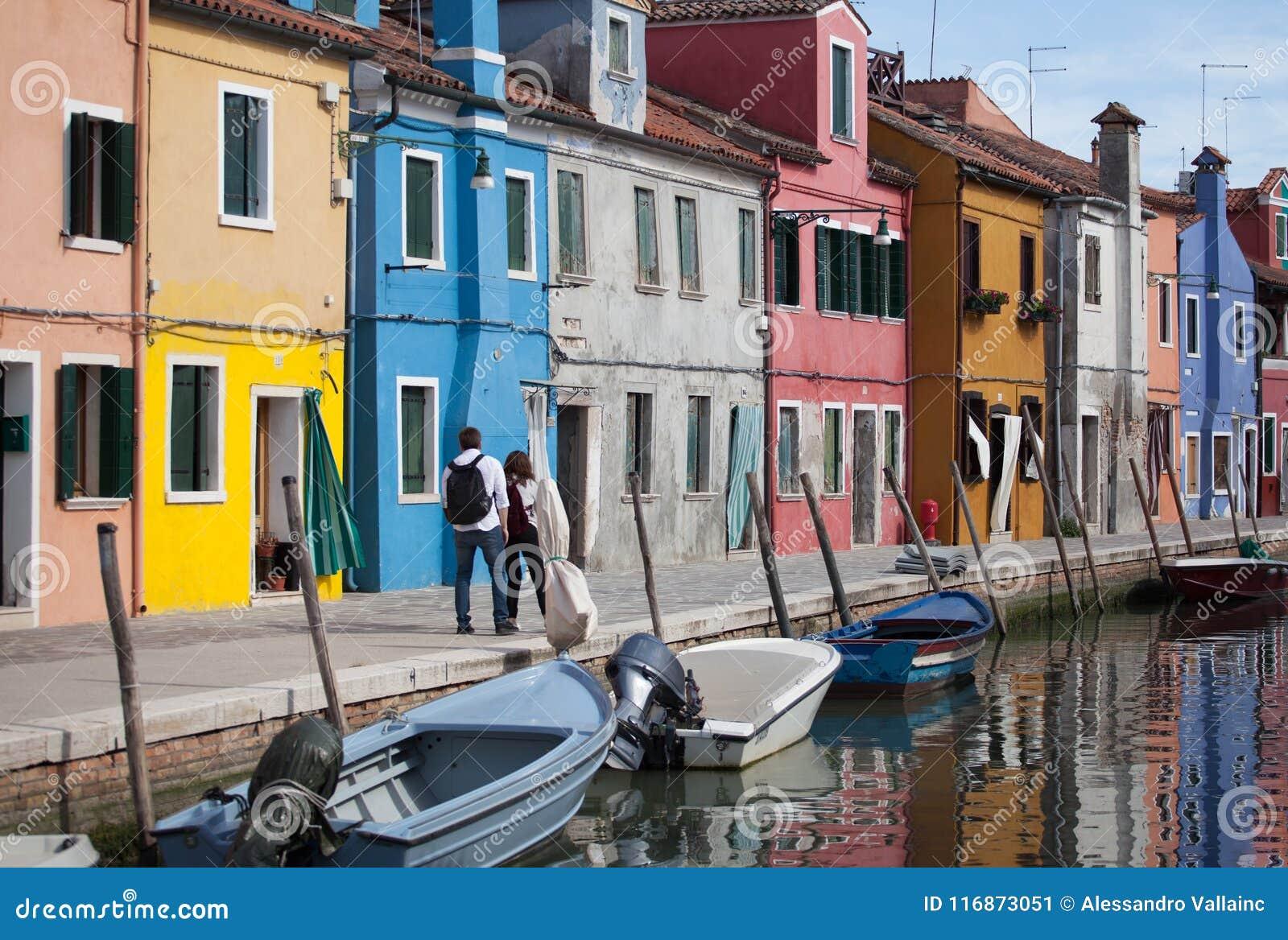 Gehende 2 Menschen - Häuser von Burano und von Reflexion im Wasser Wasserstraßen mit traditionellen Booten und bunter Fassade Ven