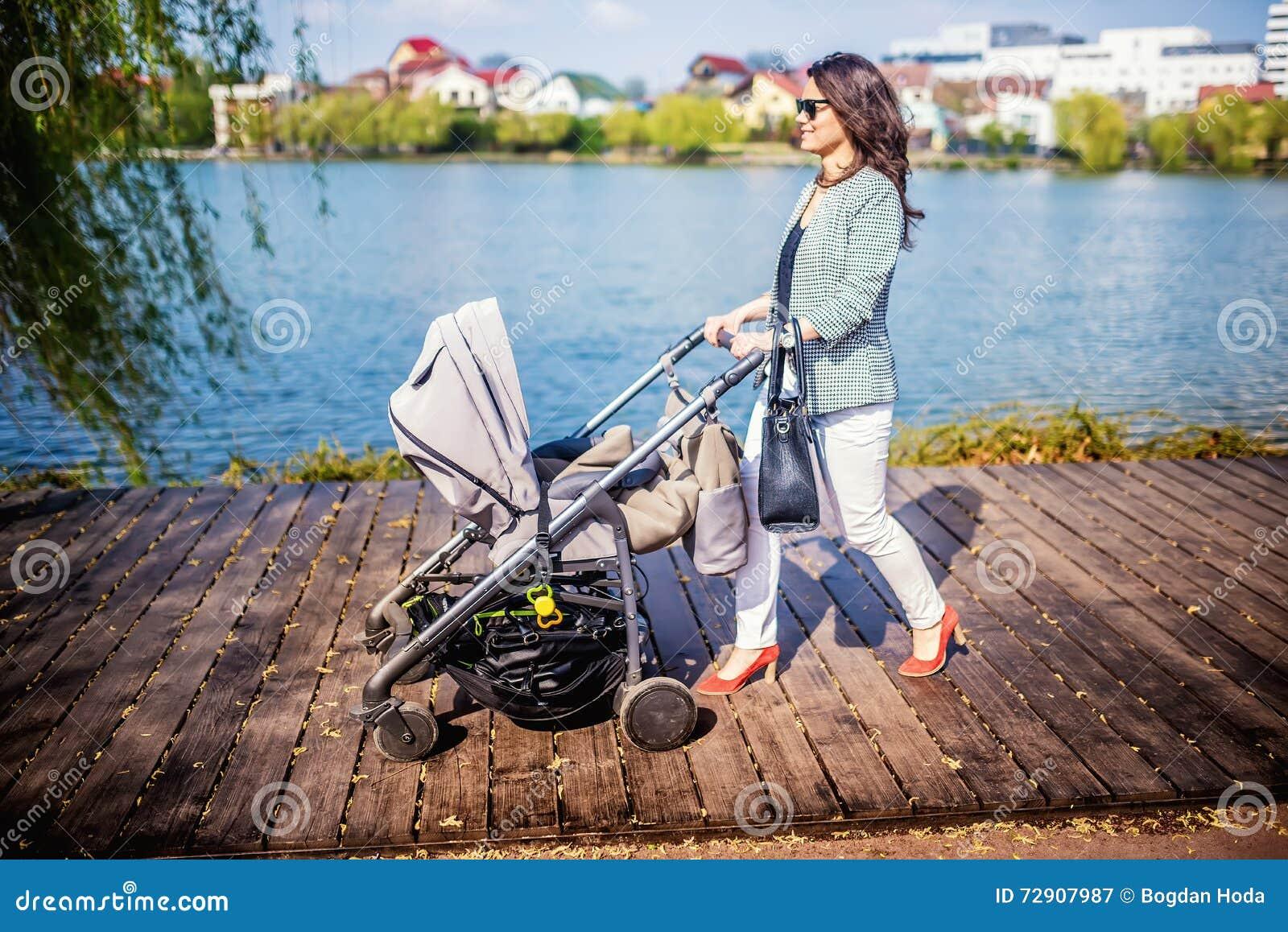Gehendes Kleinkind der schönen Mutter im städtischen Park mit neuem Kinderwagen