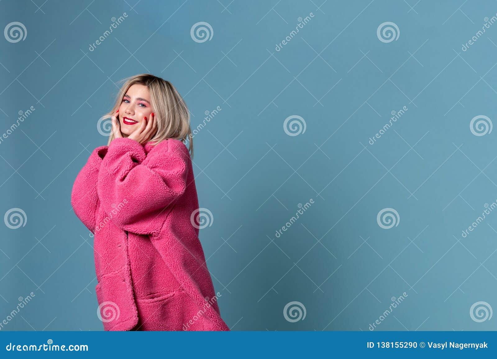 Geinteresseerd jong meisje die in modieuze roze laag camera bekijken