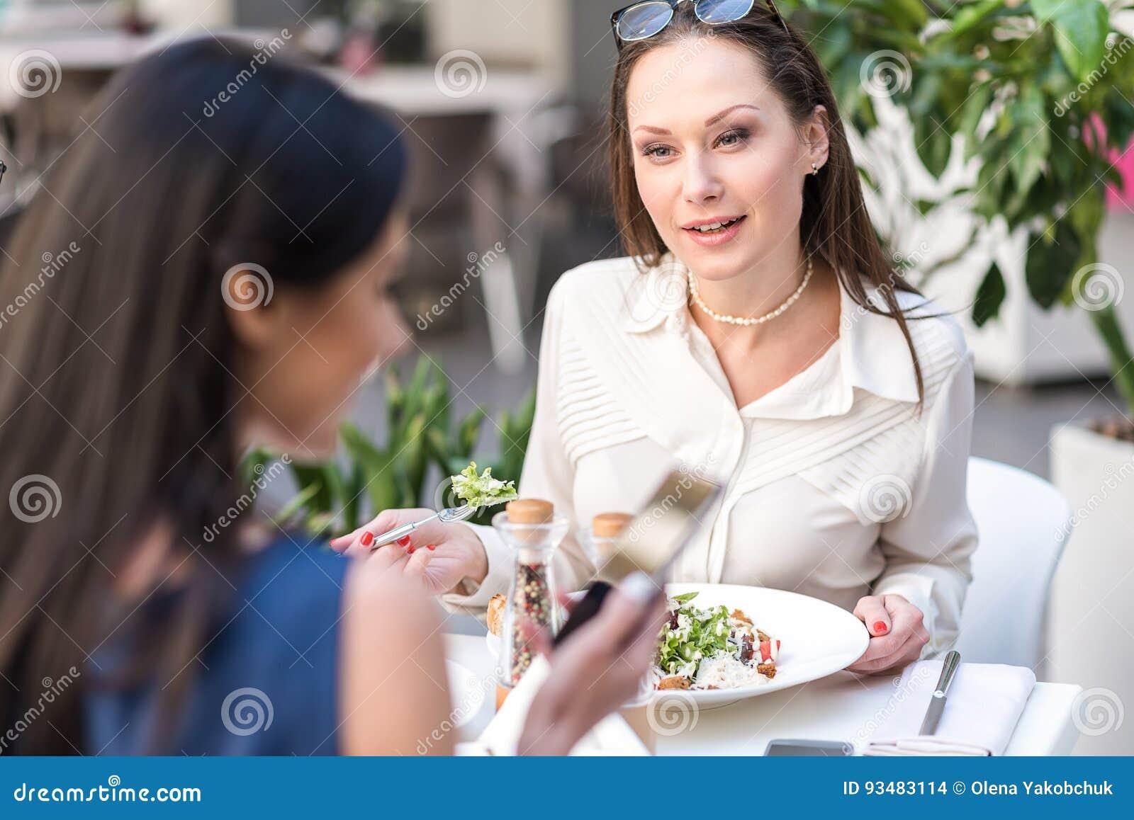 Geinteresseerde vrouwen proevende salade in koffie