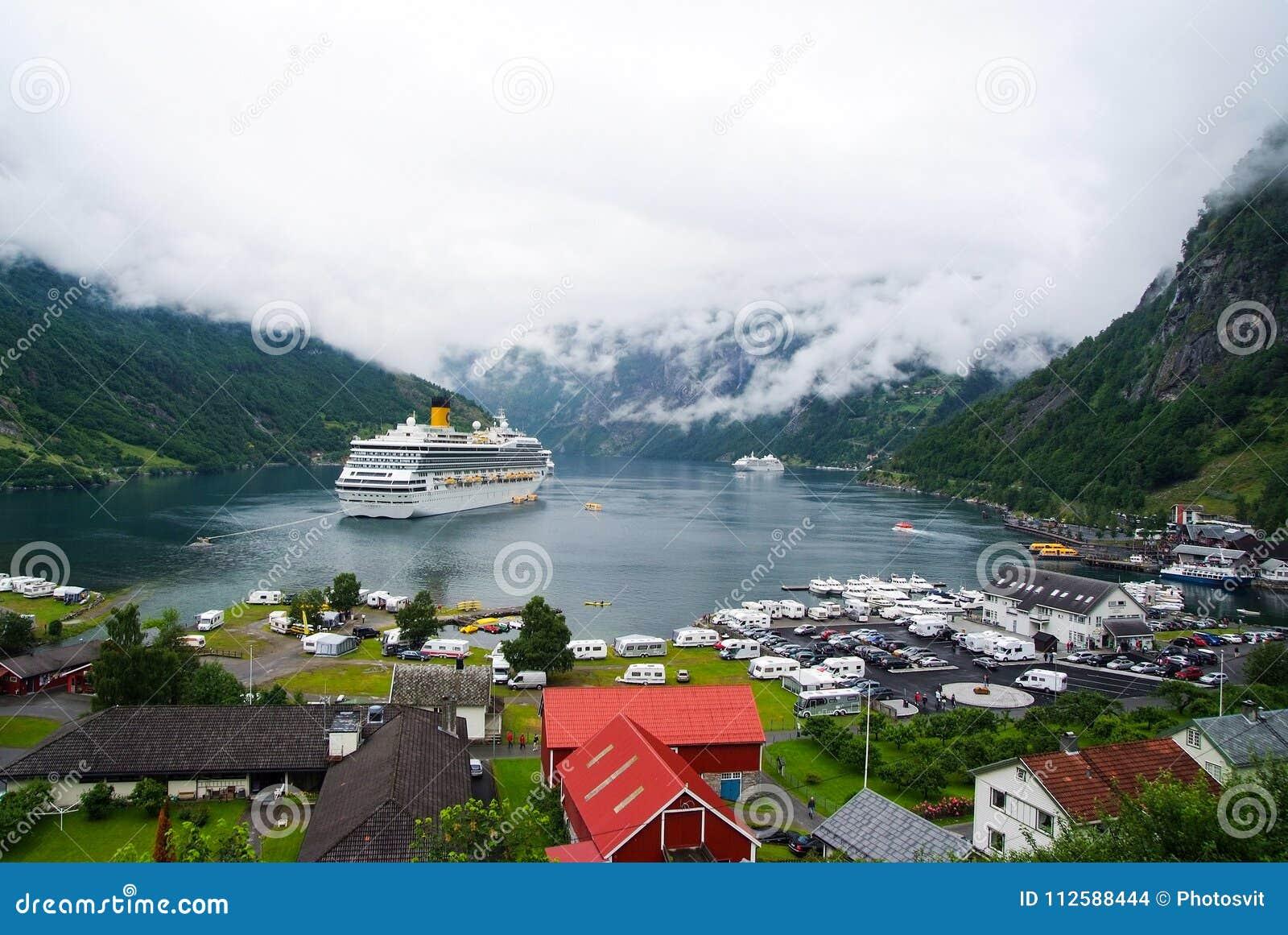 Geiranger,挪威- 2010年1月25日:船在多云天空的挪威海湾 远洋班轮在村庄港口 旅行目的地,