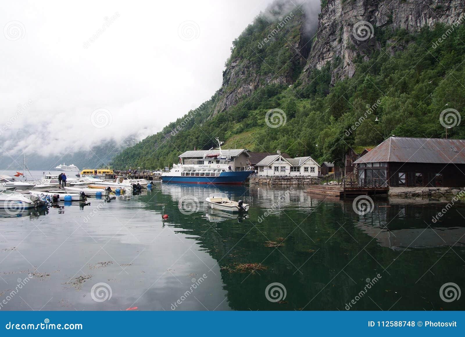 Geiranger, Noruega - 25 de enero de 2010: las casas del pueblo, barcos en el mar se abrigan en paisaje de la montaña Transporte d