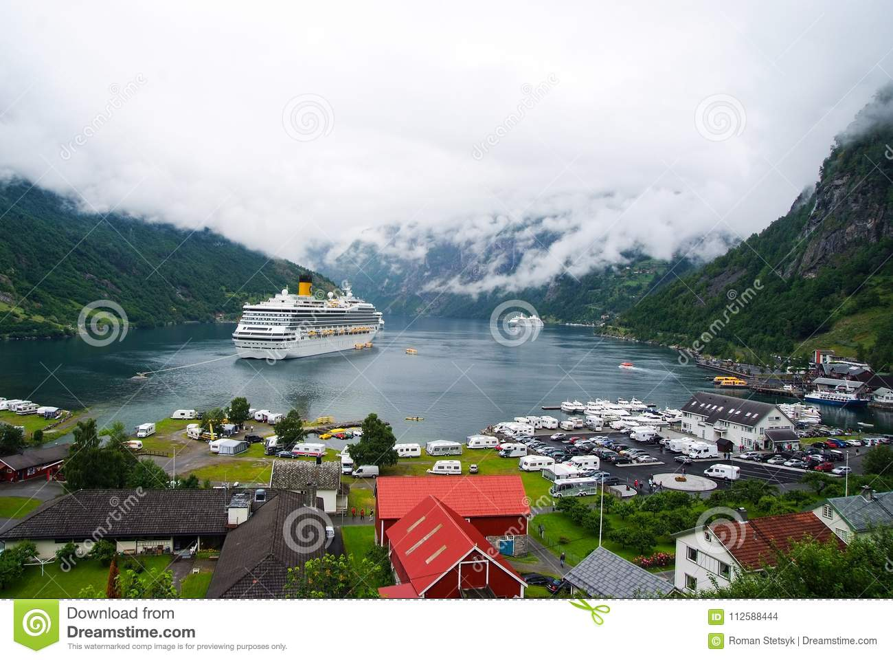 Geiranger, Norway - January 25, 2010: ship in norwegian fjord on cloudy sky. Ocean liner in village harbor. Travel destination, to