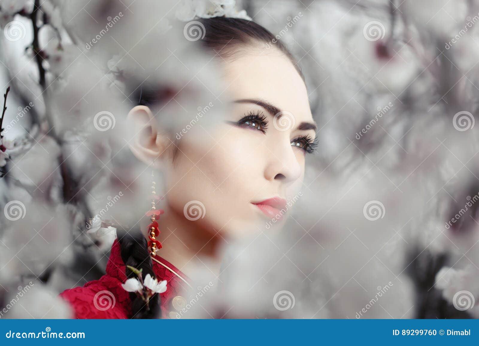 Geisha i röd kimono i sakura