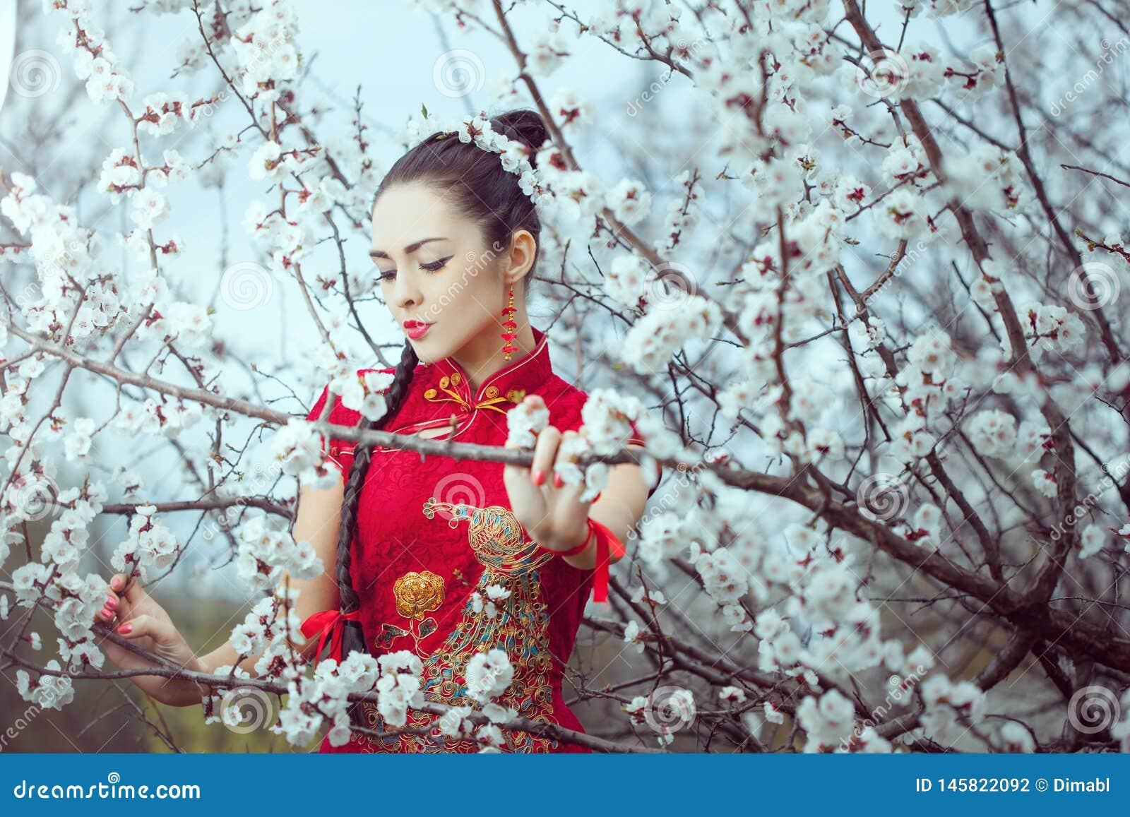 Geisha in kimono rosso a sakura
