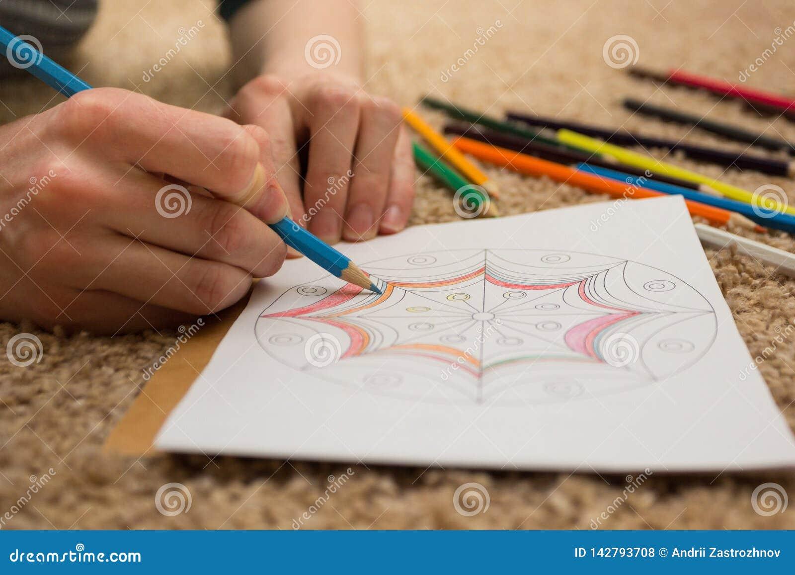 Gekleurd - antistress met blauw potlood Het meisje trekt op het tapijt