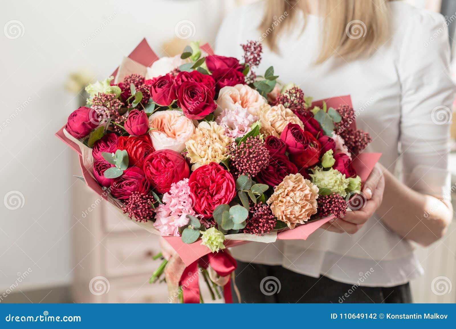 Gekleurd boeket van hoogst rood mooie luxebos van gemengde bloemen in de hand van de vrouw het werk van de bloemist bij a