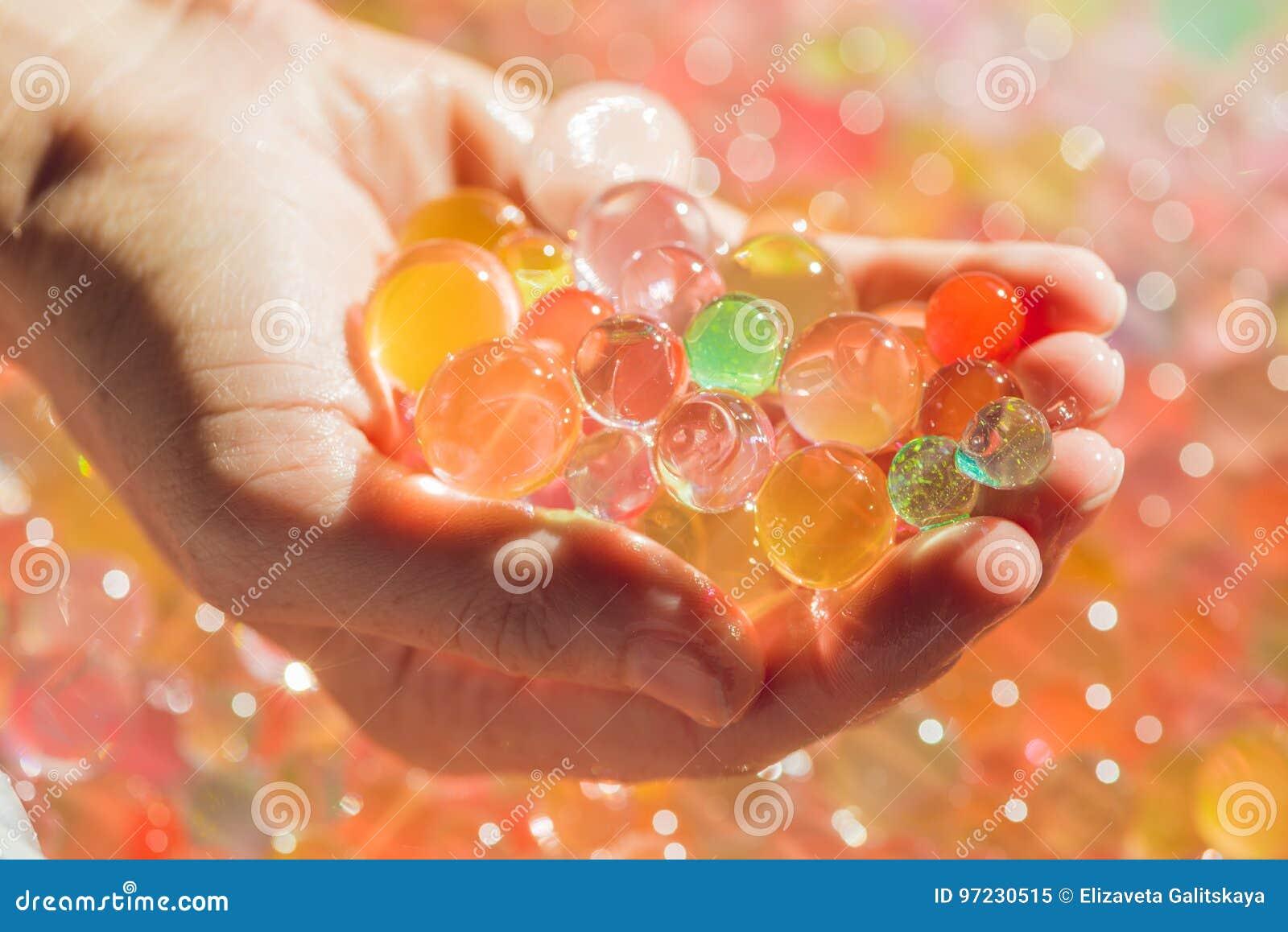 Gekleurde ballen van waterparels, hydrogel binnen in handen Sensorische ervaringen