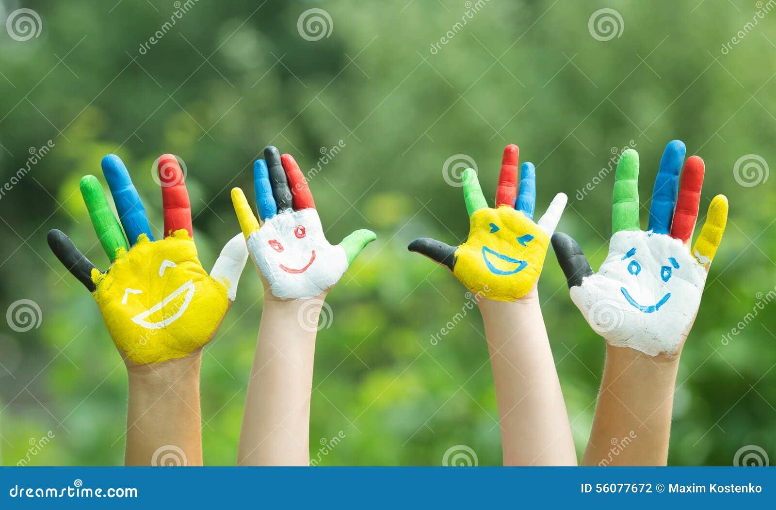 Gekleurde die handen met glimlach in kleurrijke verven worden geschilderd