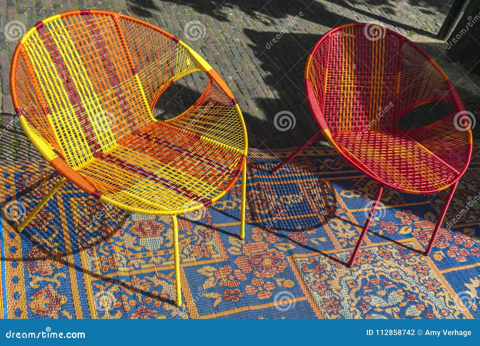 Gekleurde rieten stoel op een deken stock foto afbeelding