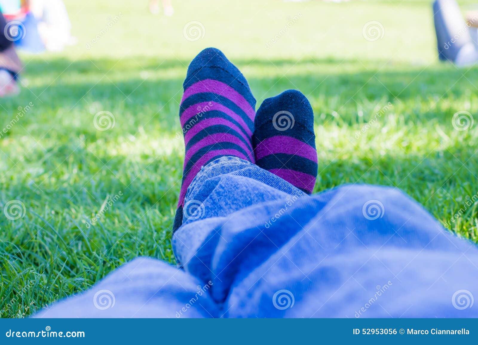 Gekleurde sokken van een tiener die in een park rust