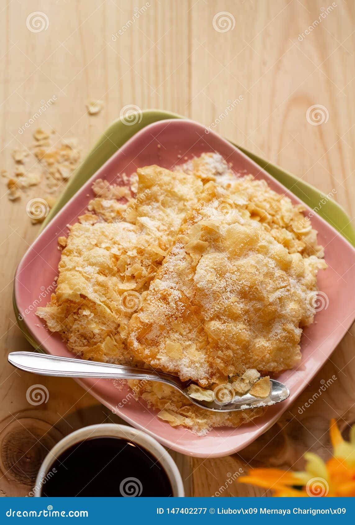 Geknisterte knusperige Pl?tzchen mit Zucker auf einer Platte und einem Tasse Kaffee auf einem Holztisch Kopieren Sie Platz