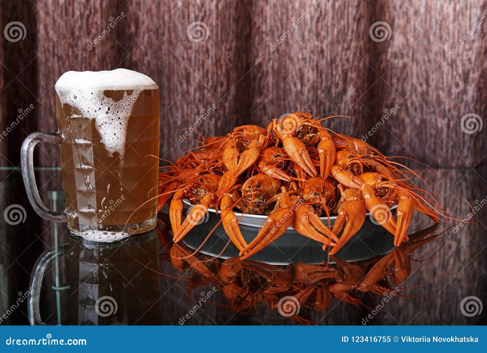 Gekookte rivierkreeften en mok met koud bier