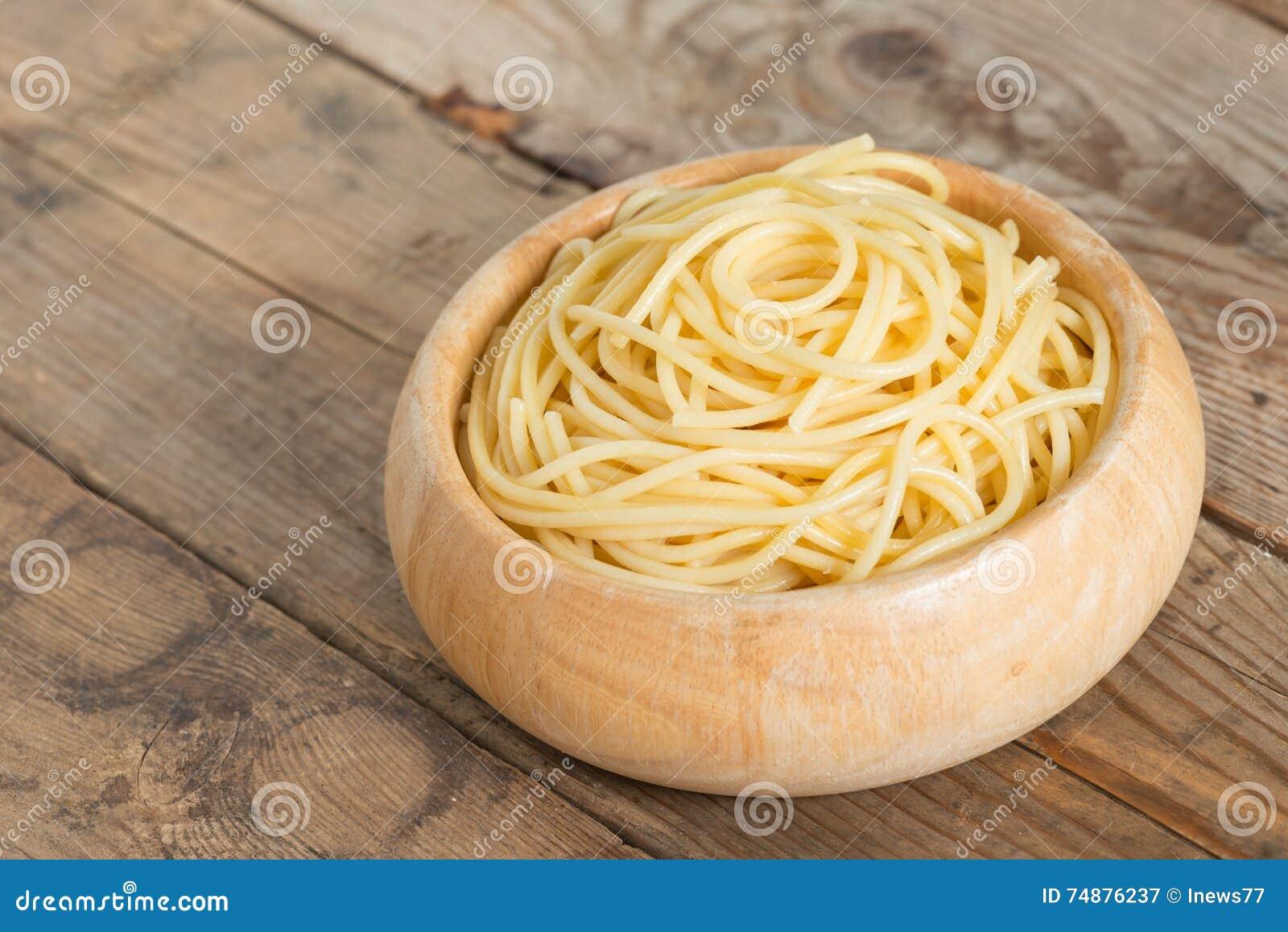 Gekookte spaghetti in houten kom