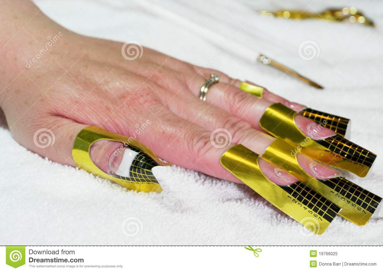 Hand on a white towel prepared for gel nail application.