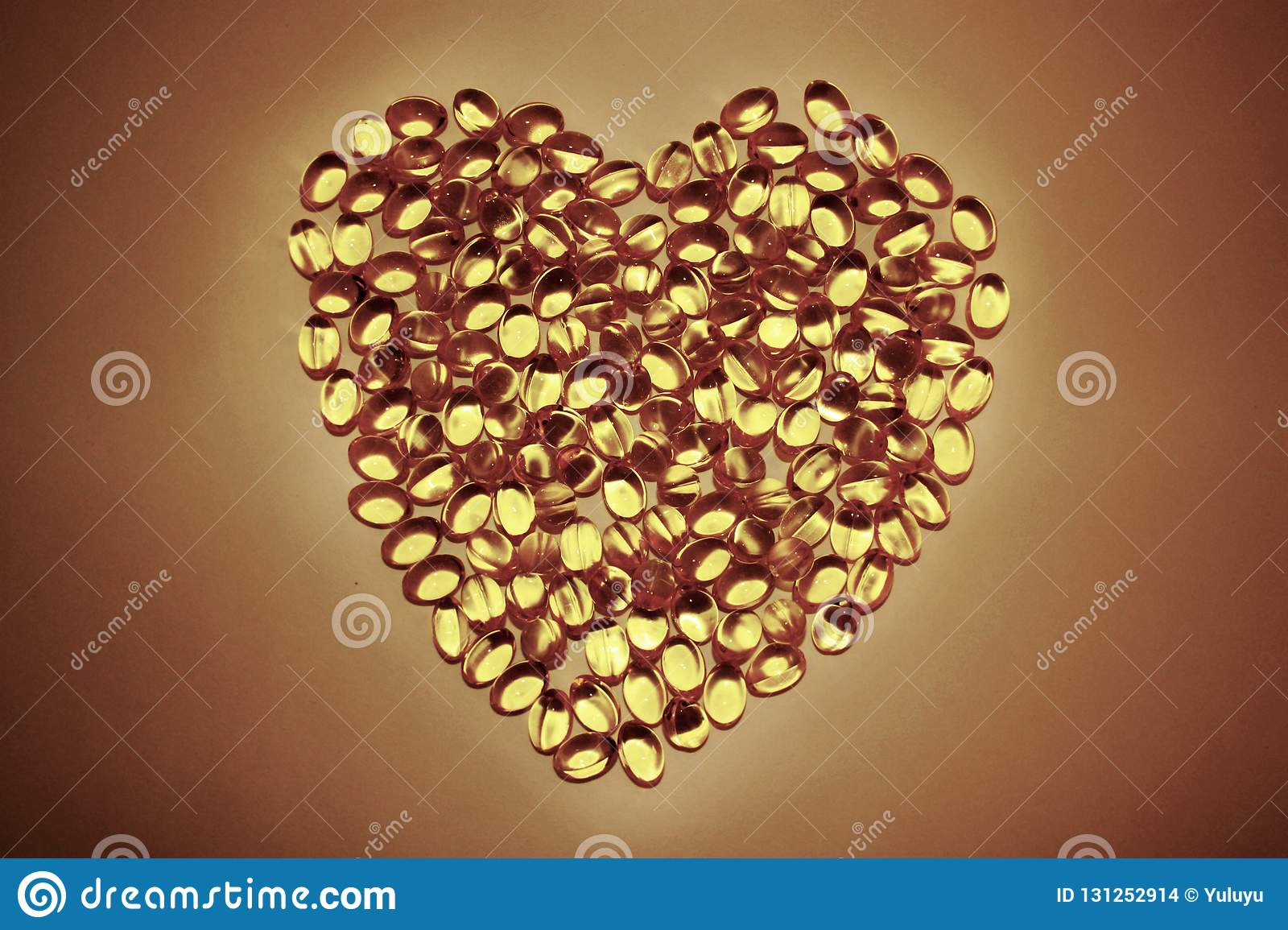Gel pills lying in the shape of a heart on white background, yellow capsules omega 3.