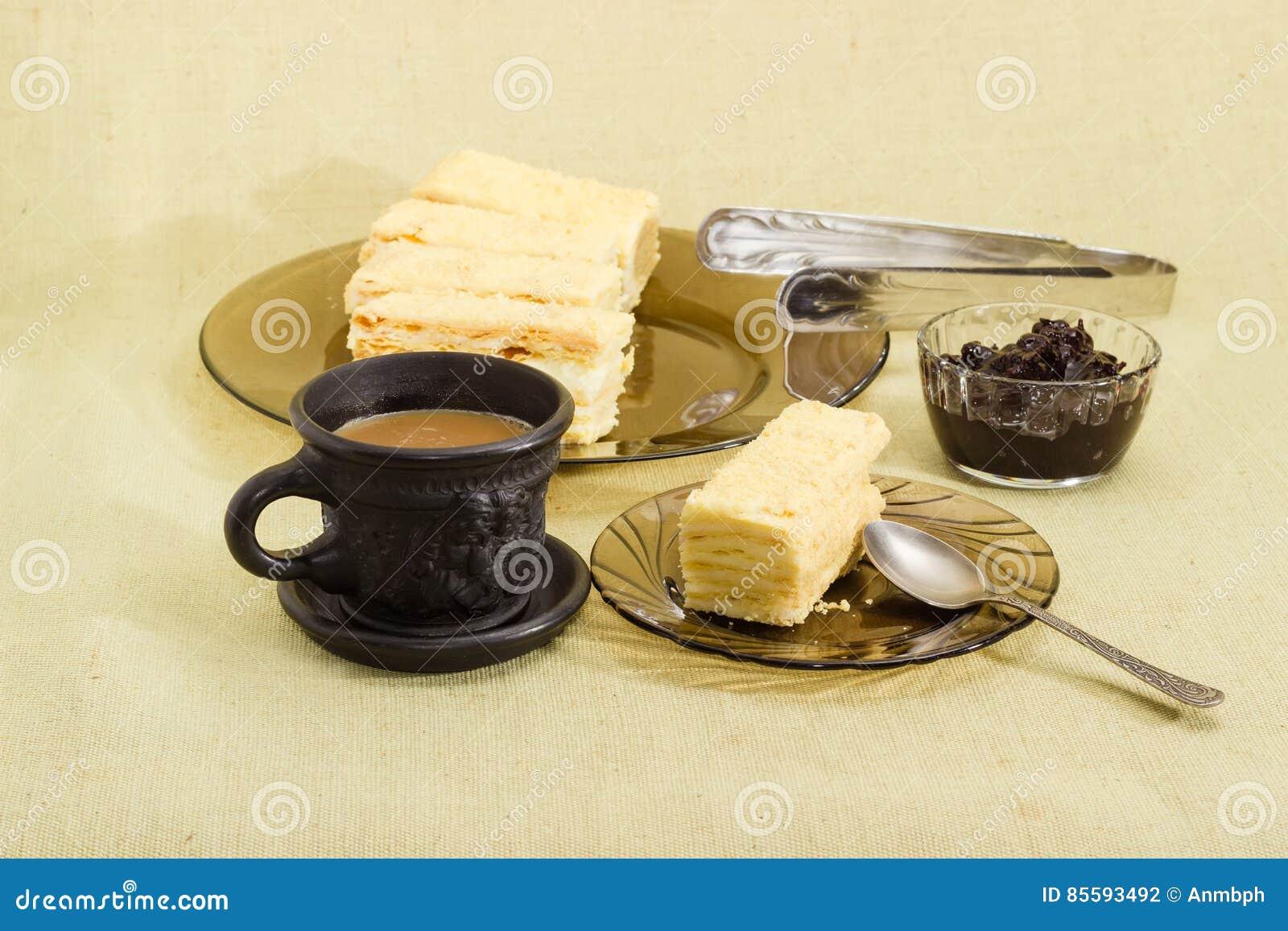 Gelaagd biscuitgebak, koffie met melk, jam