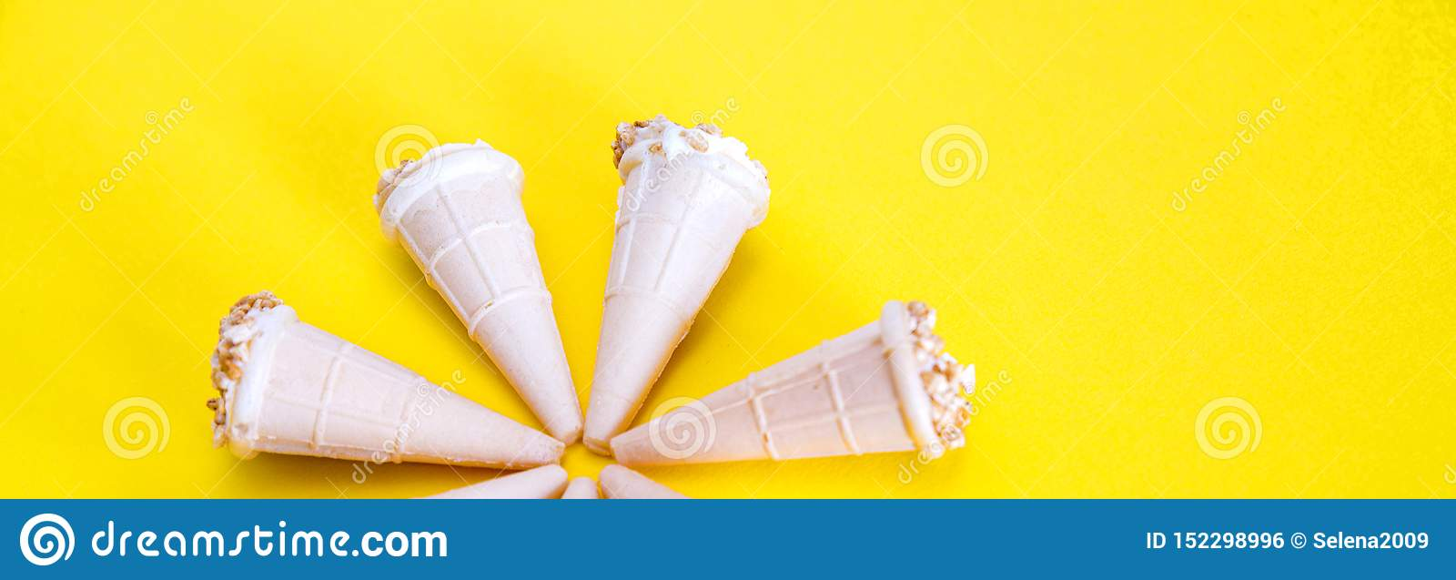 Gelado com as porcas em uns copos do waffle Cones do waffle isolados em um fundo amarelo, close-up, panorama largo