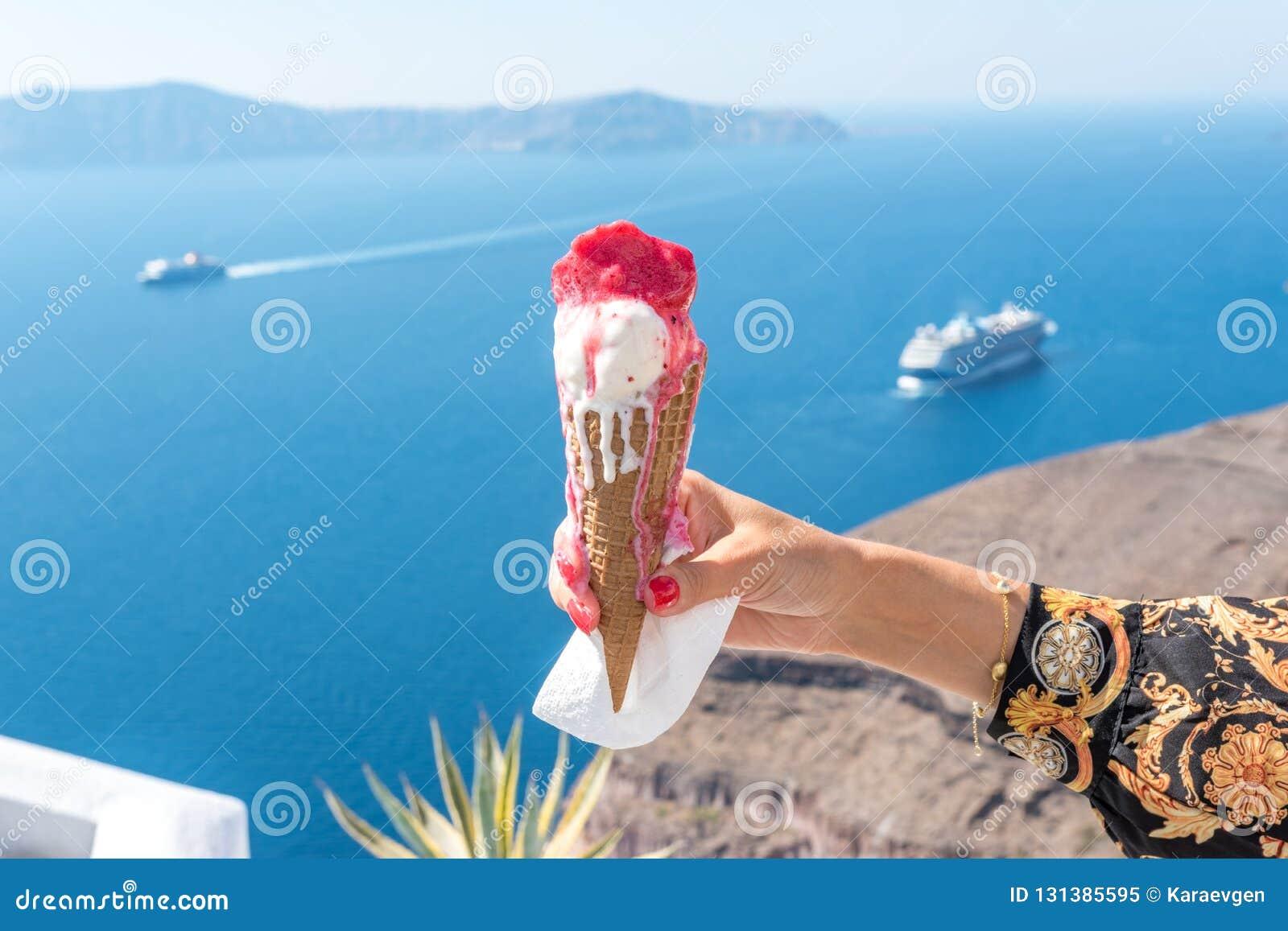 Gelado em um cone do waffle na mão da mulher no fundo da ilha de Santorini e no Caldera no Mar Egeu