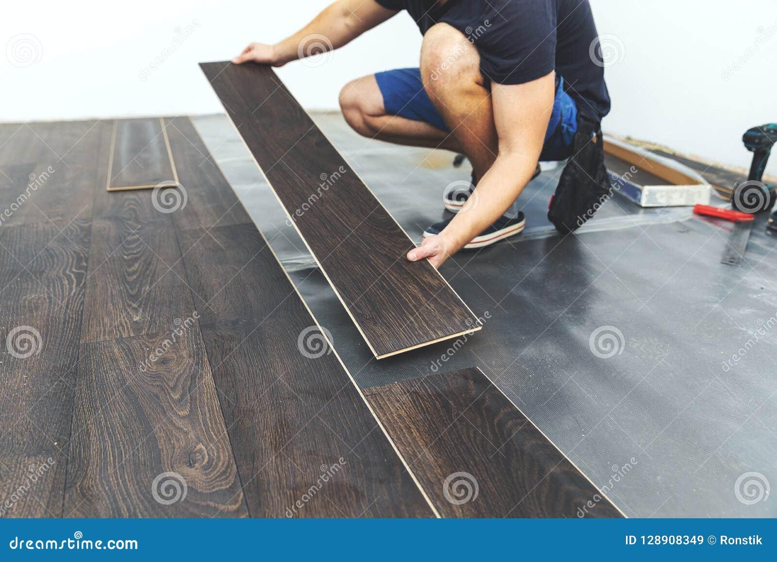 Gelamineerde bevloering arbeider die nieuwe vloer installeren