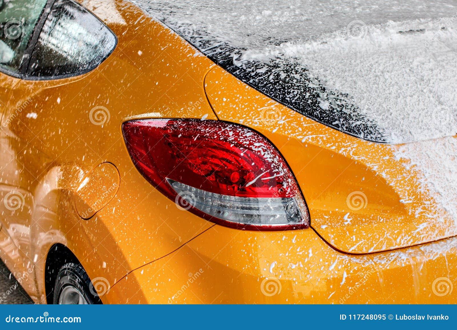Gelbe Autoheckscheibe vollständig bedeckt mit starkem weißem shamp